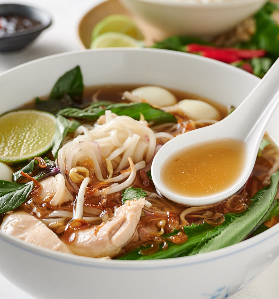 Spoonful of broth over bowl of pho ga.