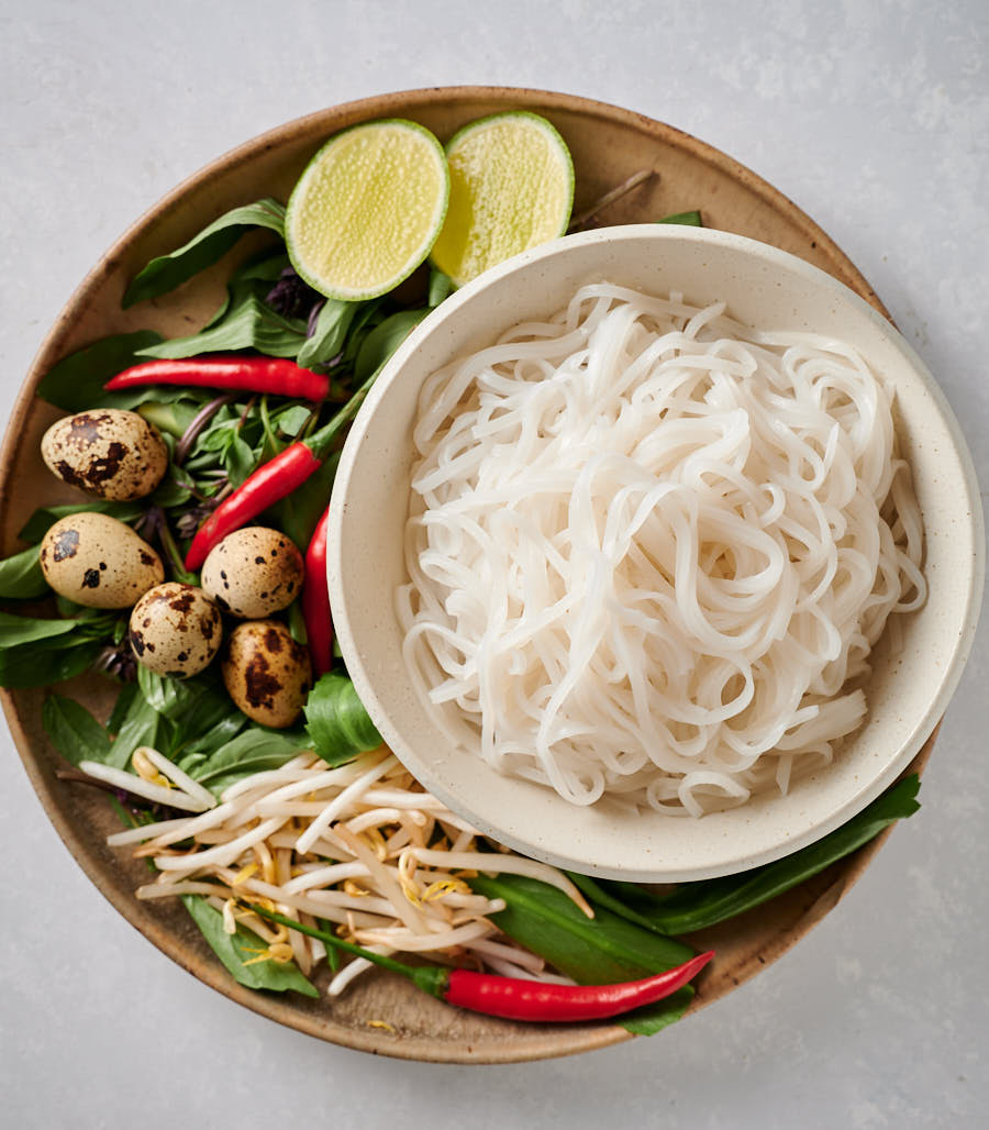Top shot of rice noodles, red chilies, herbs, quail eggs, limes and bean sprouts.