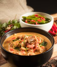 thai red chicken curry in a black bowl front view