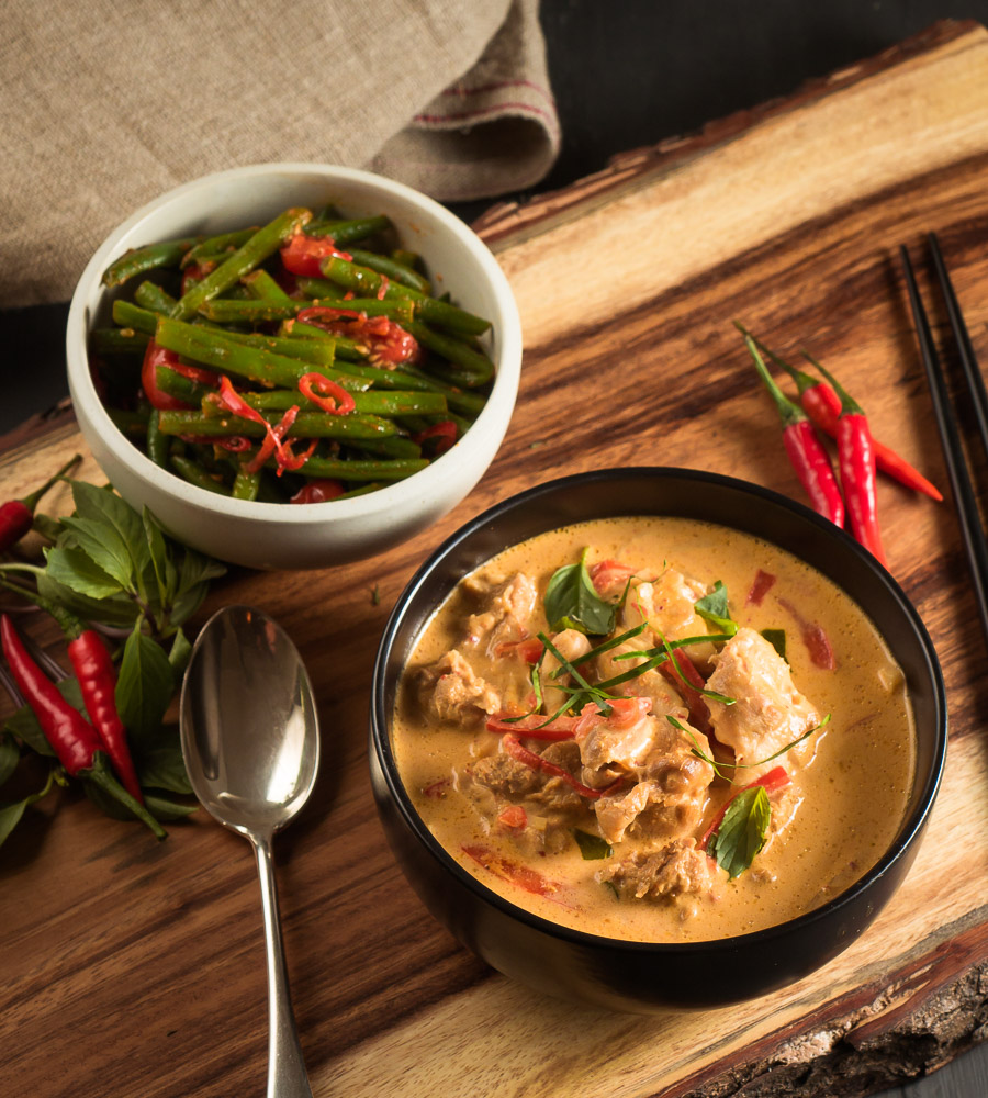thai red chicken curry in a black bowl with chilies and thai basil