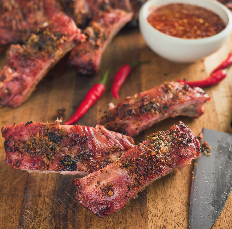 Thai ribs on cutting board with knife