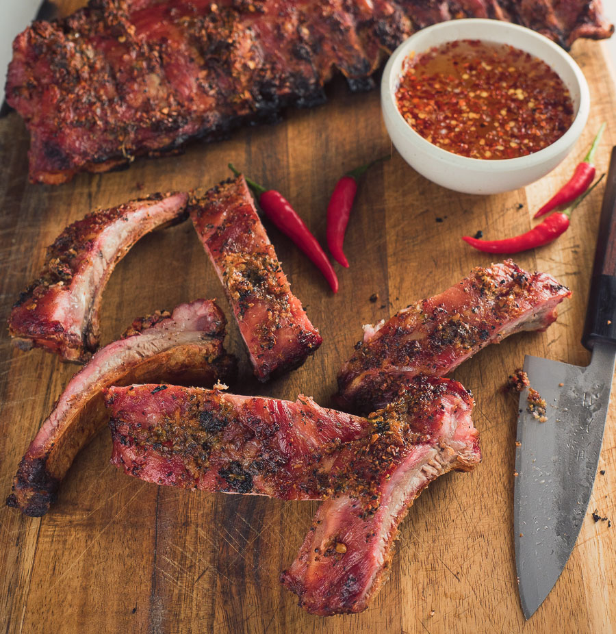 Thai ribs on a cutting board with bowl of dipping sauce