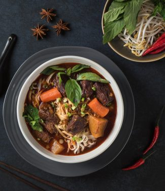 Mi bo kho in a white bowl on black background from above