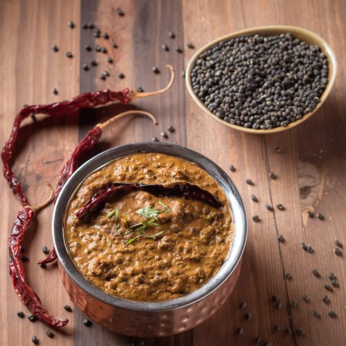 Punjabi dal makhani in a small copper pot garnished with a red chili.