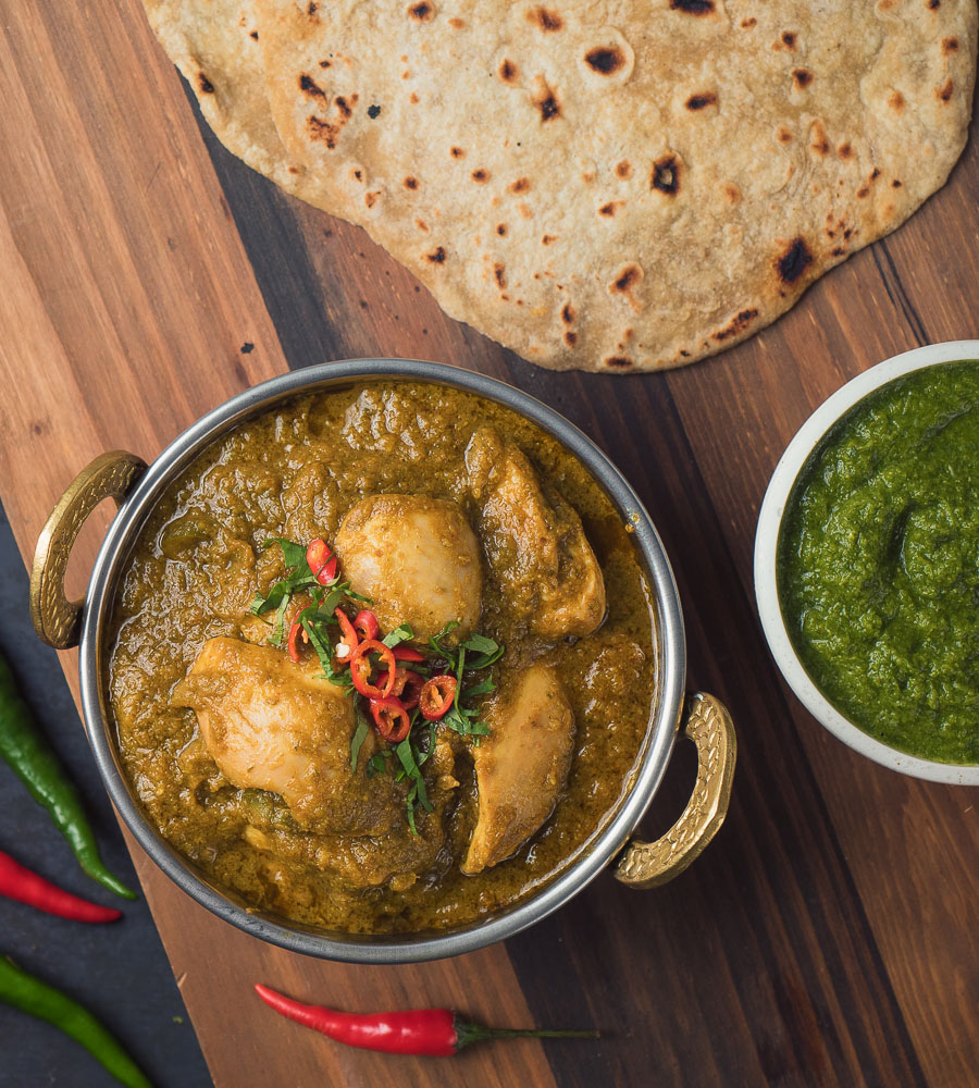 hariyali chicken curry in Indian copper bowl with chapati.