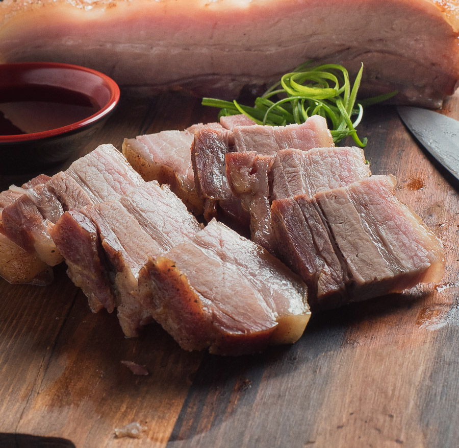 sliced pork belly on cutting board with knife and chopsticks