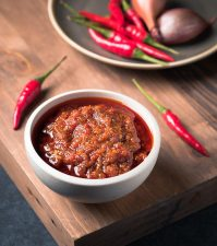 Vietnamese sate sauce in a white bowl with red chilies.