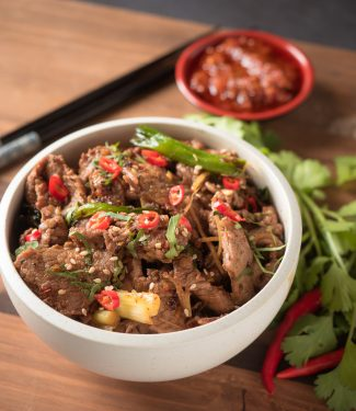 ginger beef stir fry in a white bowl close up