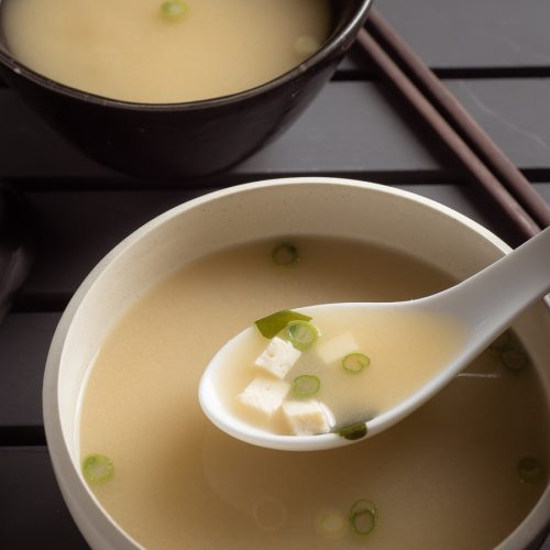 Japanese miso soup in a white bowl with spoon.