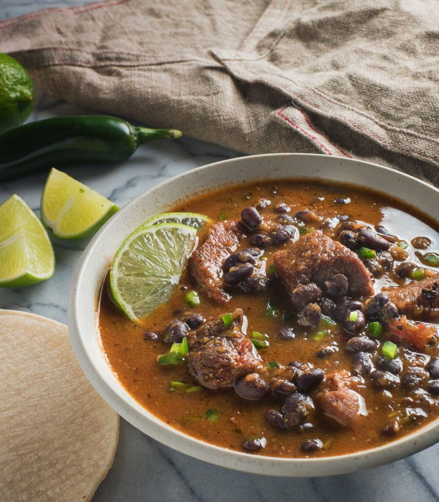 Mexican pork and black bean stew garnished with lime slices