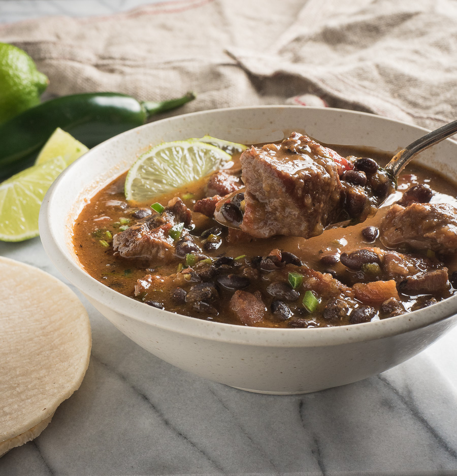 Taking a spoonful of Mexican pork and black bean stew.