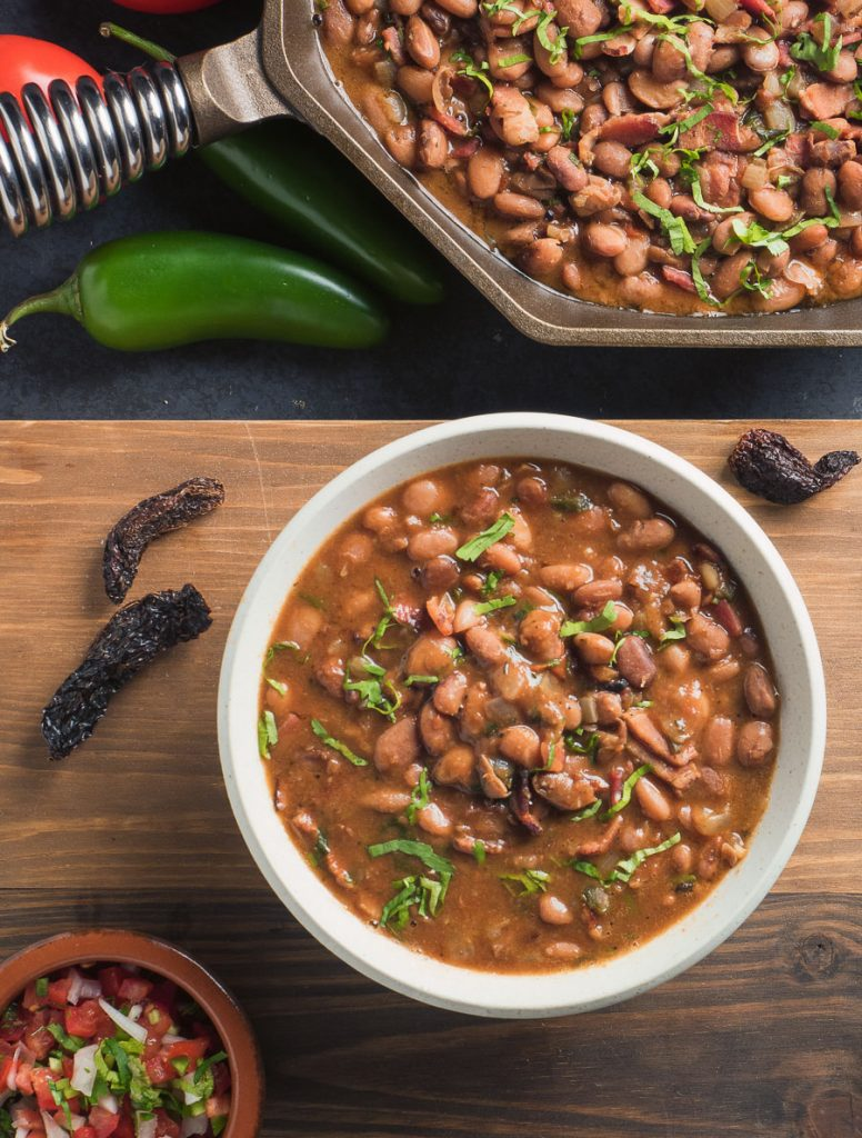 Mexican charro beans in a white bowl. View from above.