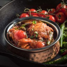 Nearly restaurant chicken jalfrezi in an Indian copper bowl - front view.