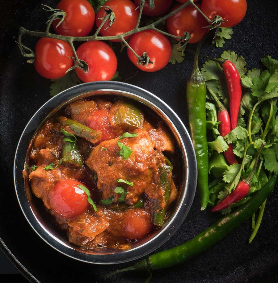 Nearly restaurant chicken jalfrezi in an Indian copper bowl - top view.