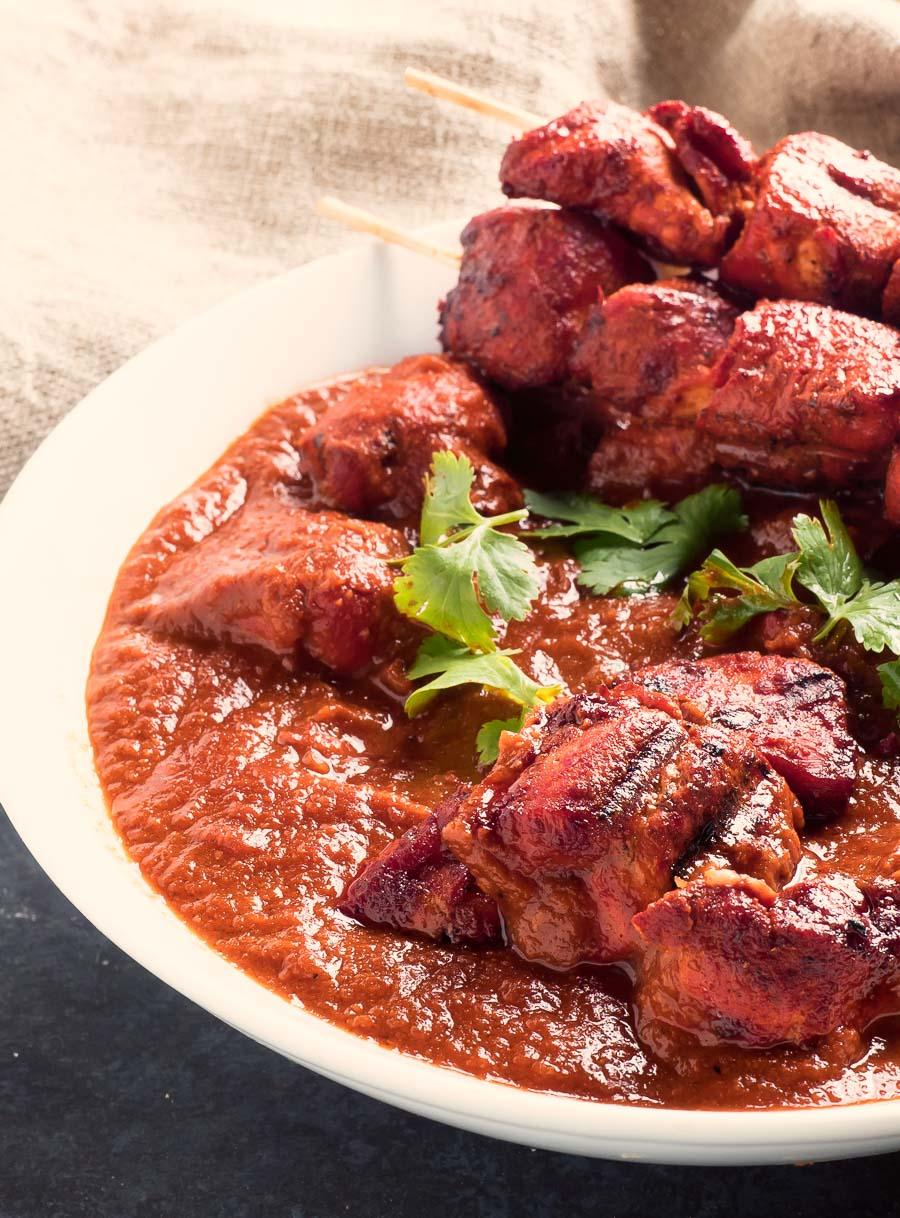 Restaurant style chicken tikka masala with chicken tikka skewers close up/