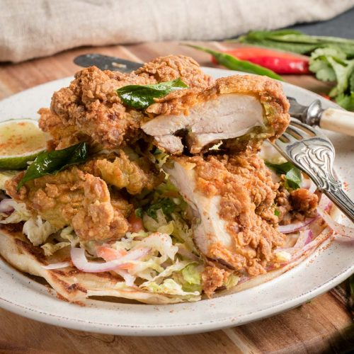 Crispy Kerala fried chicken cut with knife and fork.
