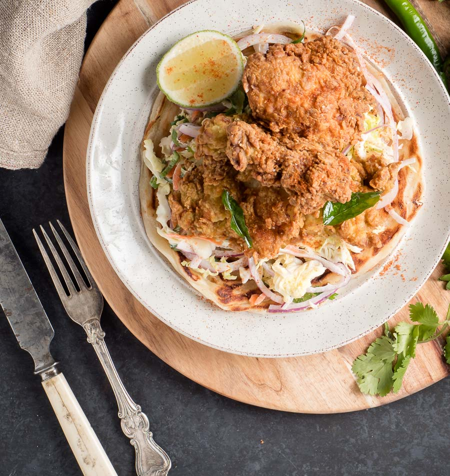 Kerala fried chicken on a bed of slaw from above.