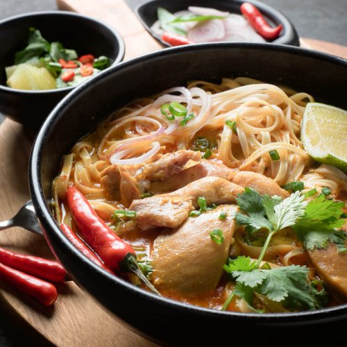 Chicken Khao soi in a black bowl from the front.