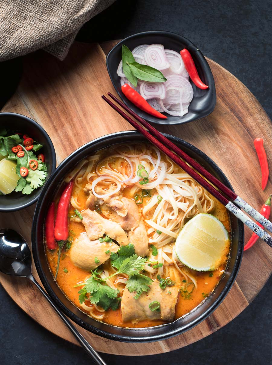 Thai chicken khao soi with garnishes from above.