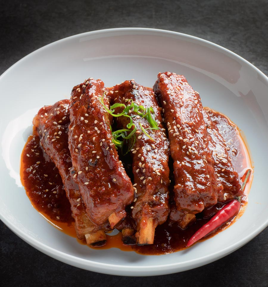 Korean braised pork ribs in a white bowl.