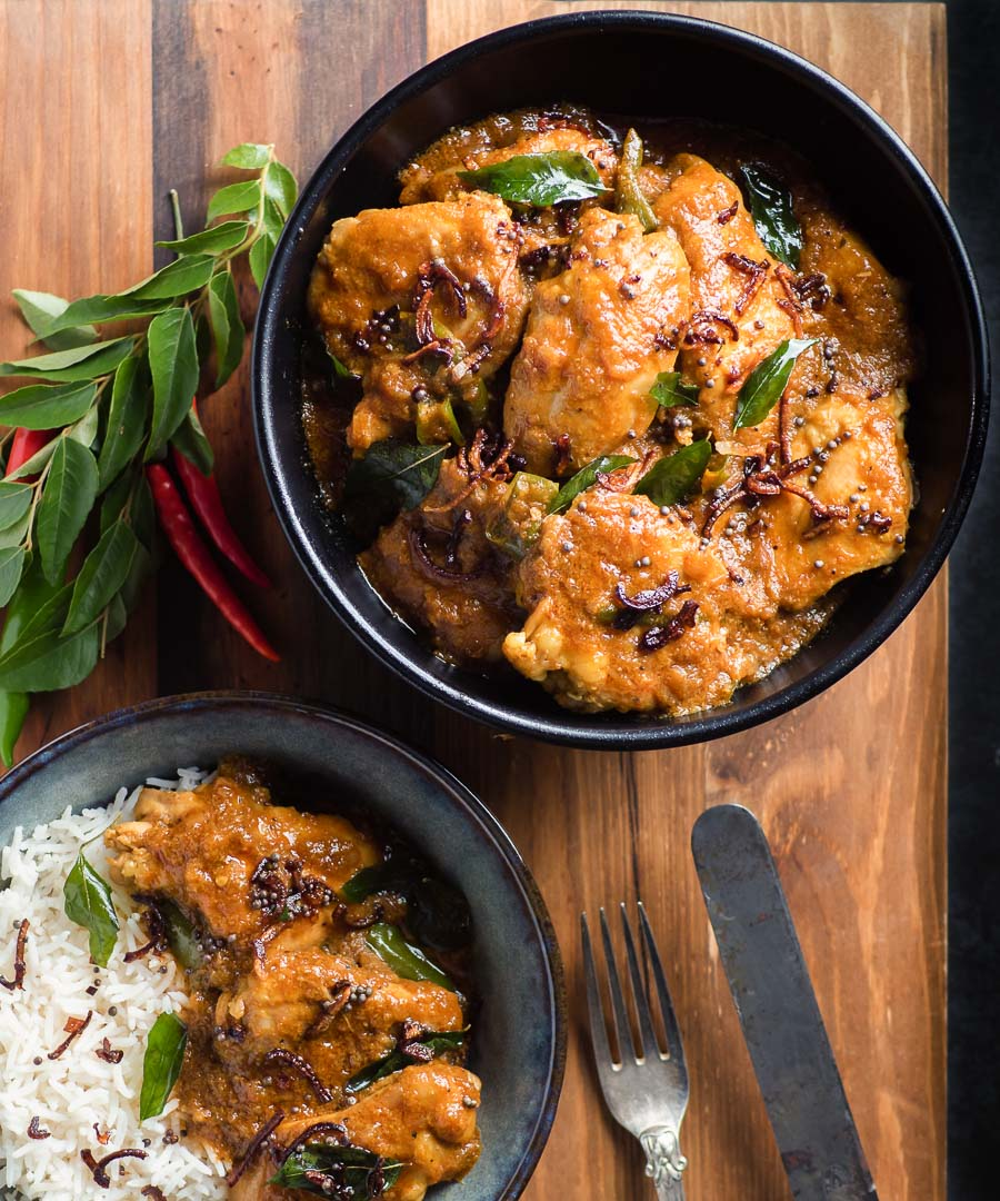 Nadan chicken curry in a black bowl from above.