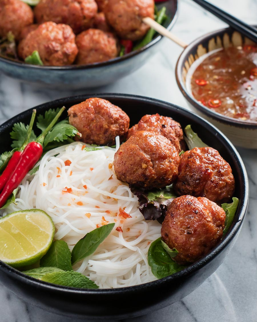 Bun cha in a black bowl from the front.