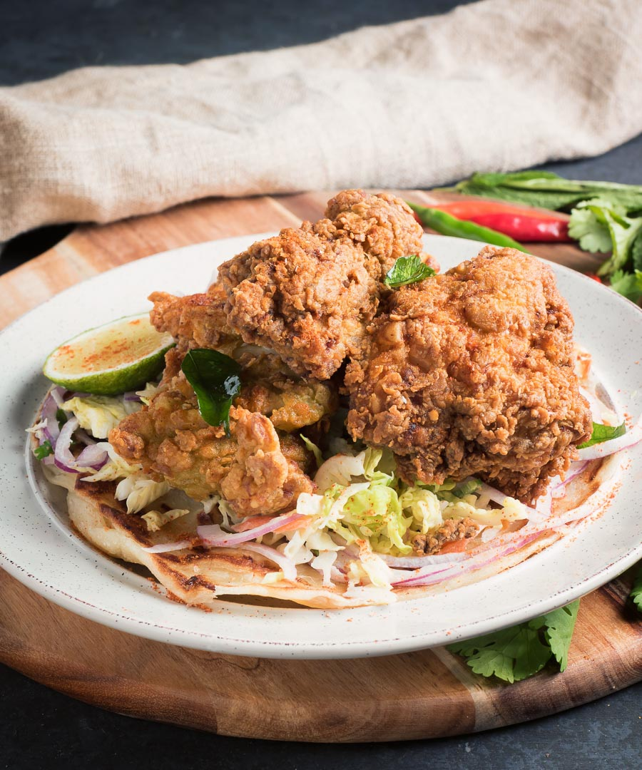 Crispy Kerala fried chicken on slaw from the front.
