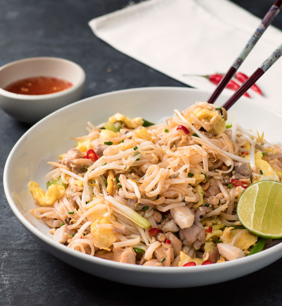 Chicken pad thai with chopsticks sticking up.