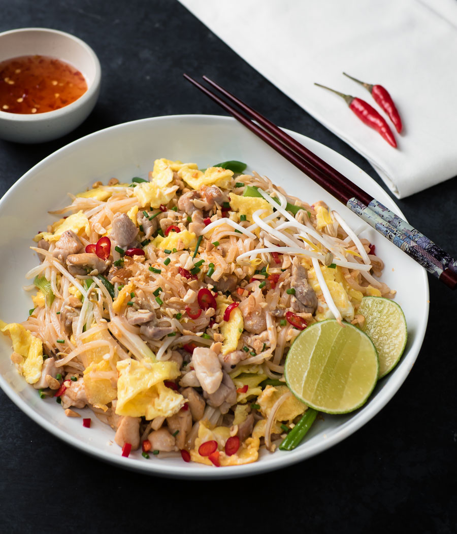 Chicken pad thai in a white bowl from the front.