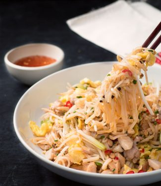 Chicken pad thai mouthful with chopsticks.