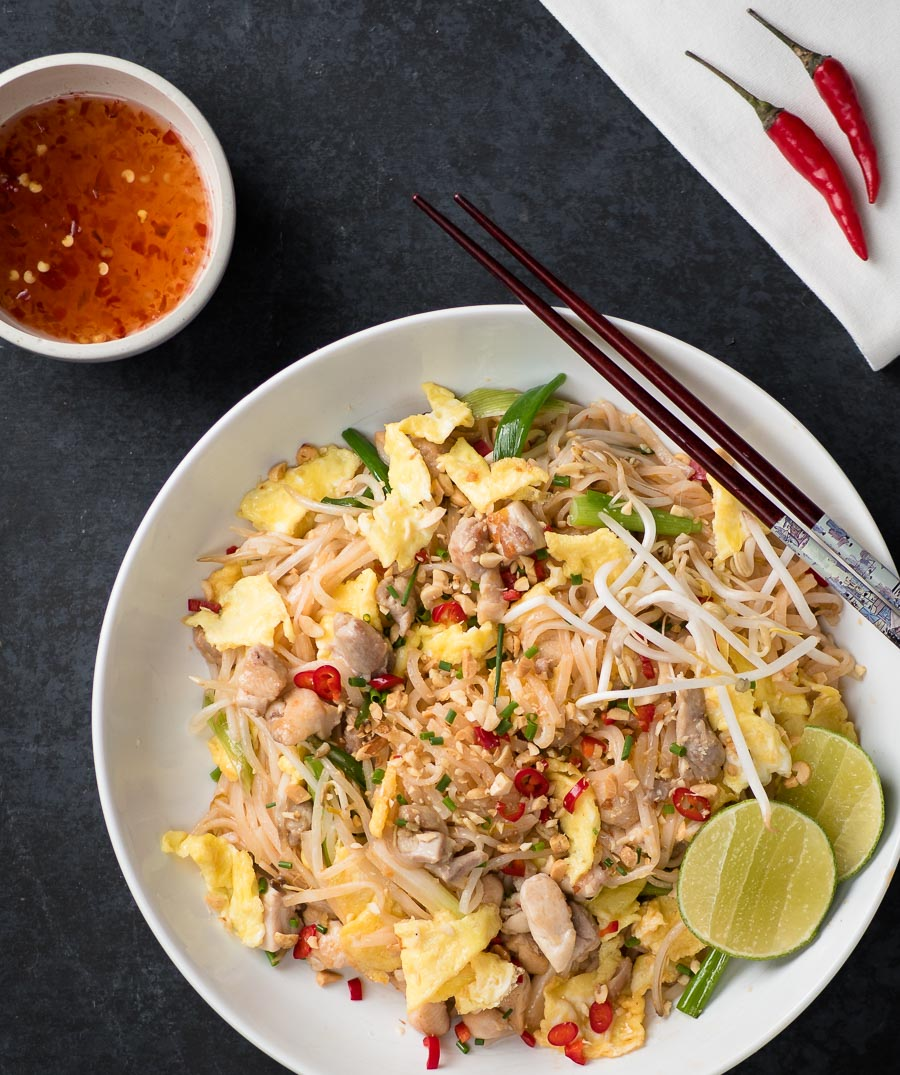 Chicken pad thai in a white bowl from above.