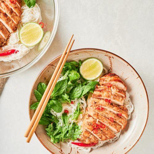 Closeup of Vietnamese lemongrass chicken in a bowl with chopsticks from above.