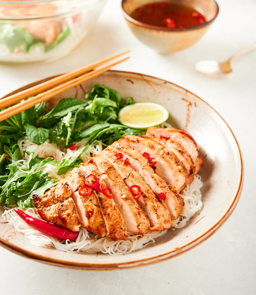 Closeup of Vietnamese lemongrass chicken in a bowl with chopsticks from the front.