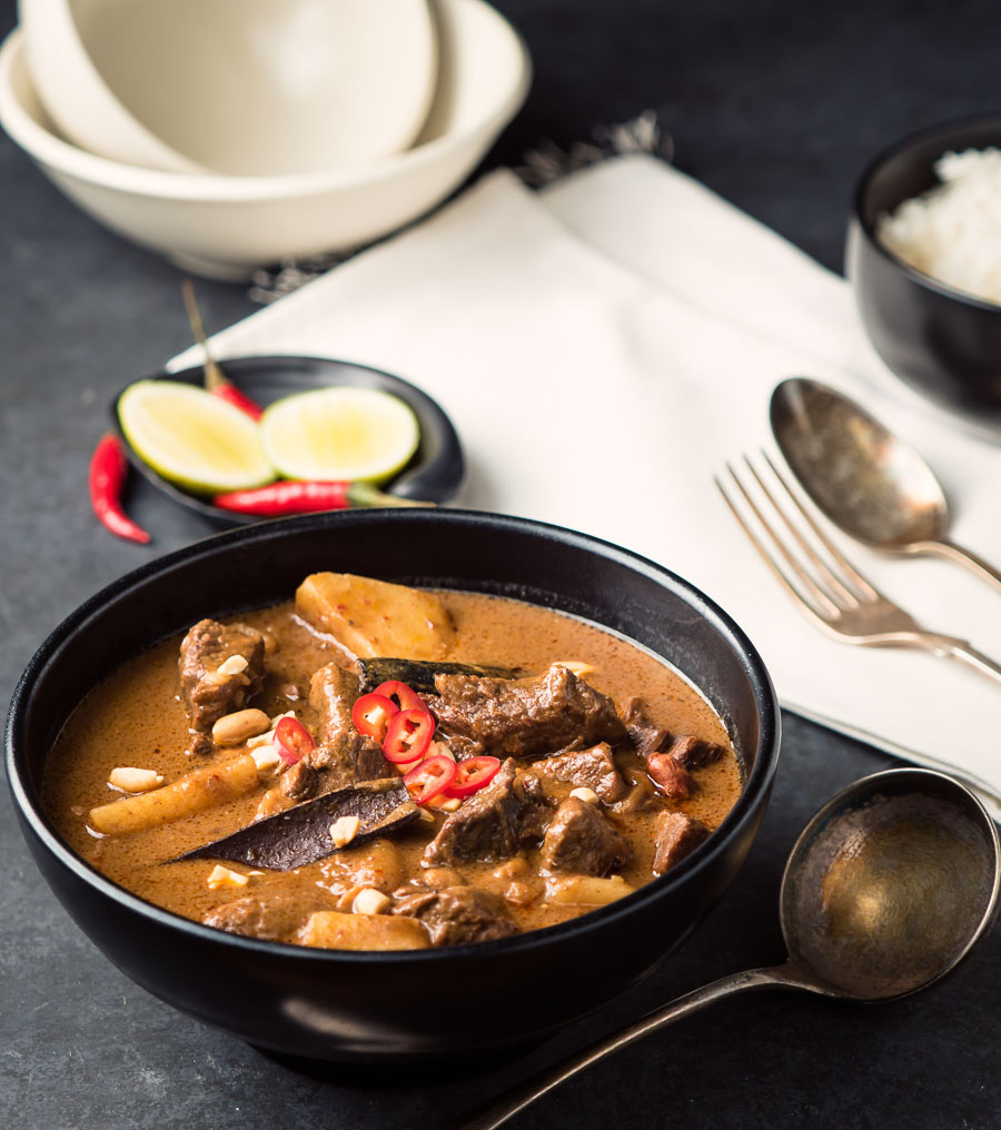 Beef massaman curry in a black bowl.