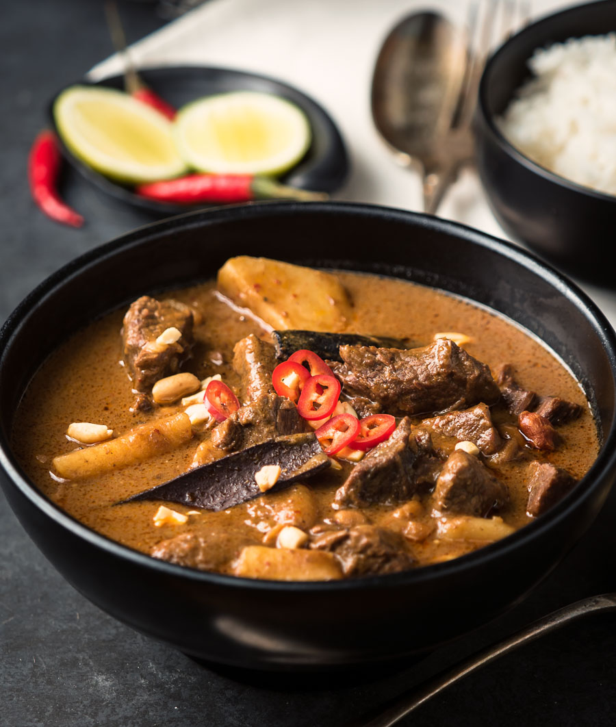 Close-up of beef massaman curry in a black bowl.