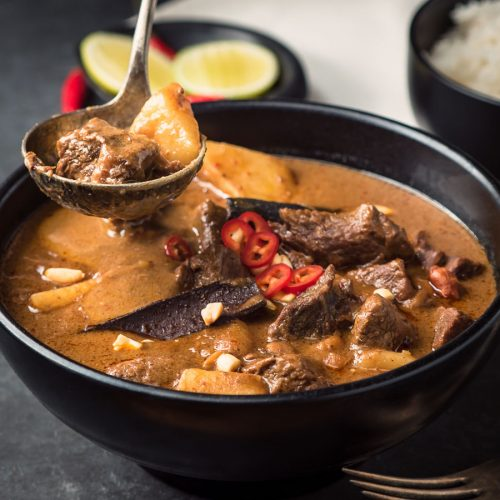 Beef massaman curry in black bowl with ladle.