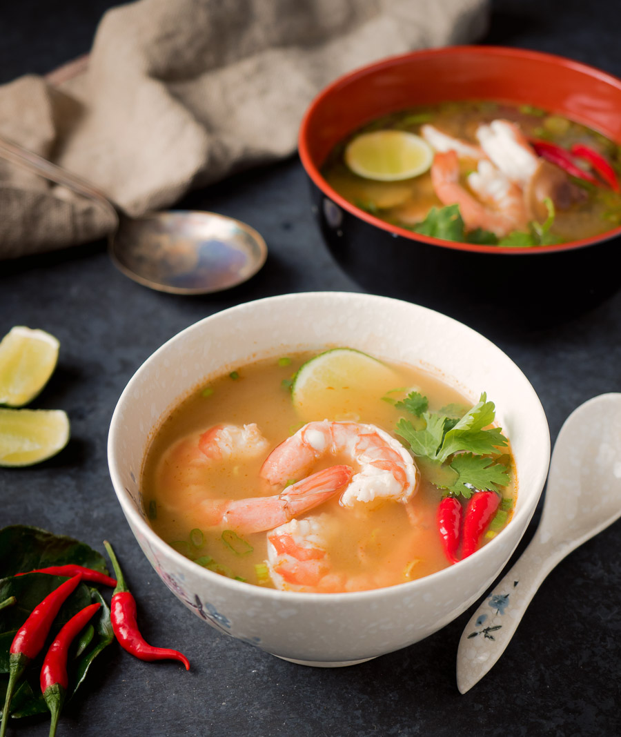 Tom yum soup in a white bowl.