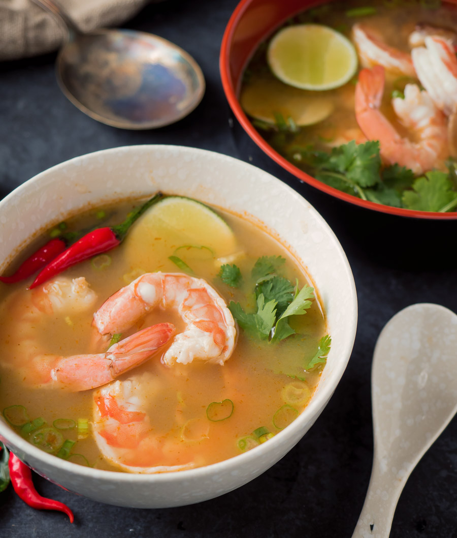 Tom yum soup in a white bowl up close.