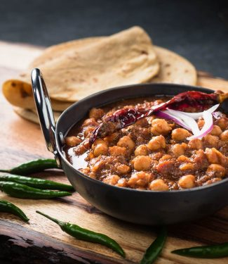 Punjabi chole masala in an Indian iron dish from the front.
