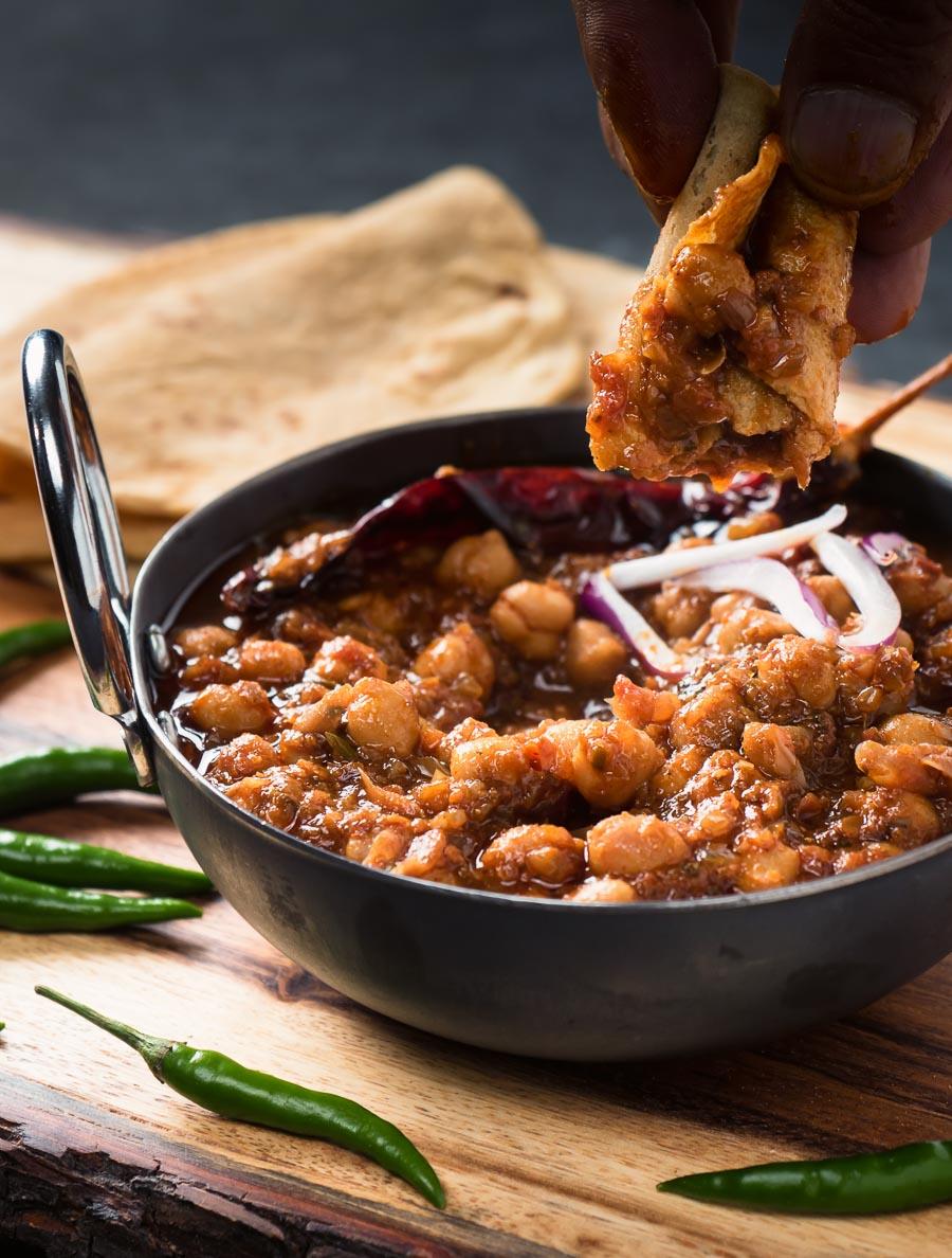 Dipping chapati into Punjabi chole masala