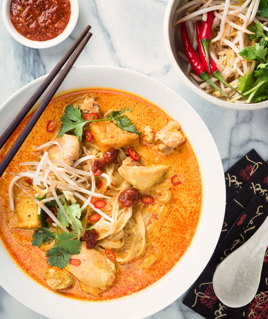 Laksa coconut curry soup from above - garnished with cilantro, red chilies and bean sprouts.
