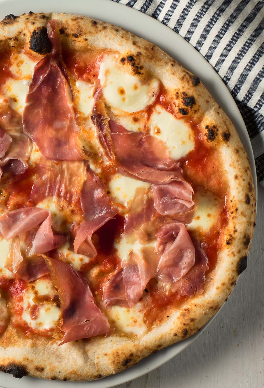 Neapolitan pizza with prosciutto and mozzarella