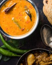 South Indian sambar in a metal bowl from above.
