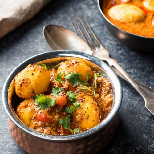 Bombay potatoes in a copper Indian bowl with spoon and fork.