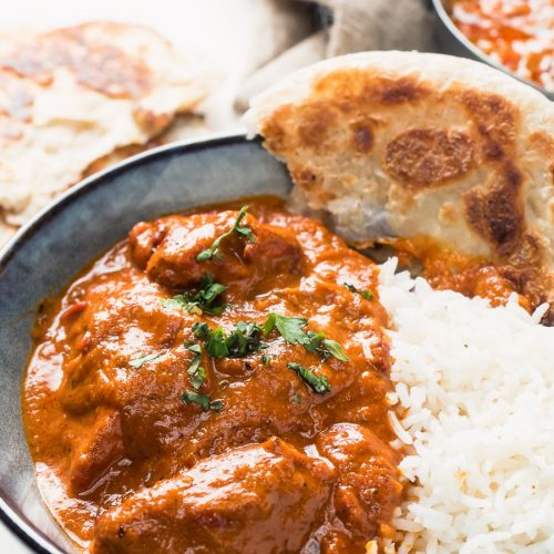 Restaurant butter chicken in a bowl with rice and paratha