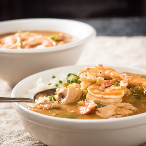 Spoon in a bowl of gumbo with chicken and sausage