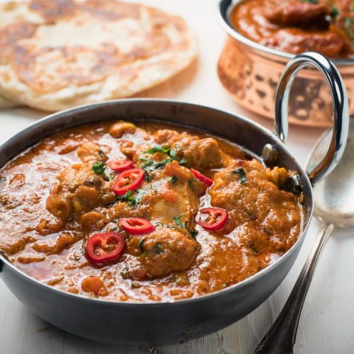 Restaurant karahi chicken in an Indian styles serving dish.
