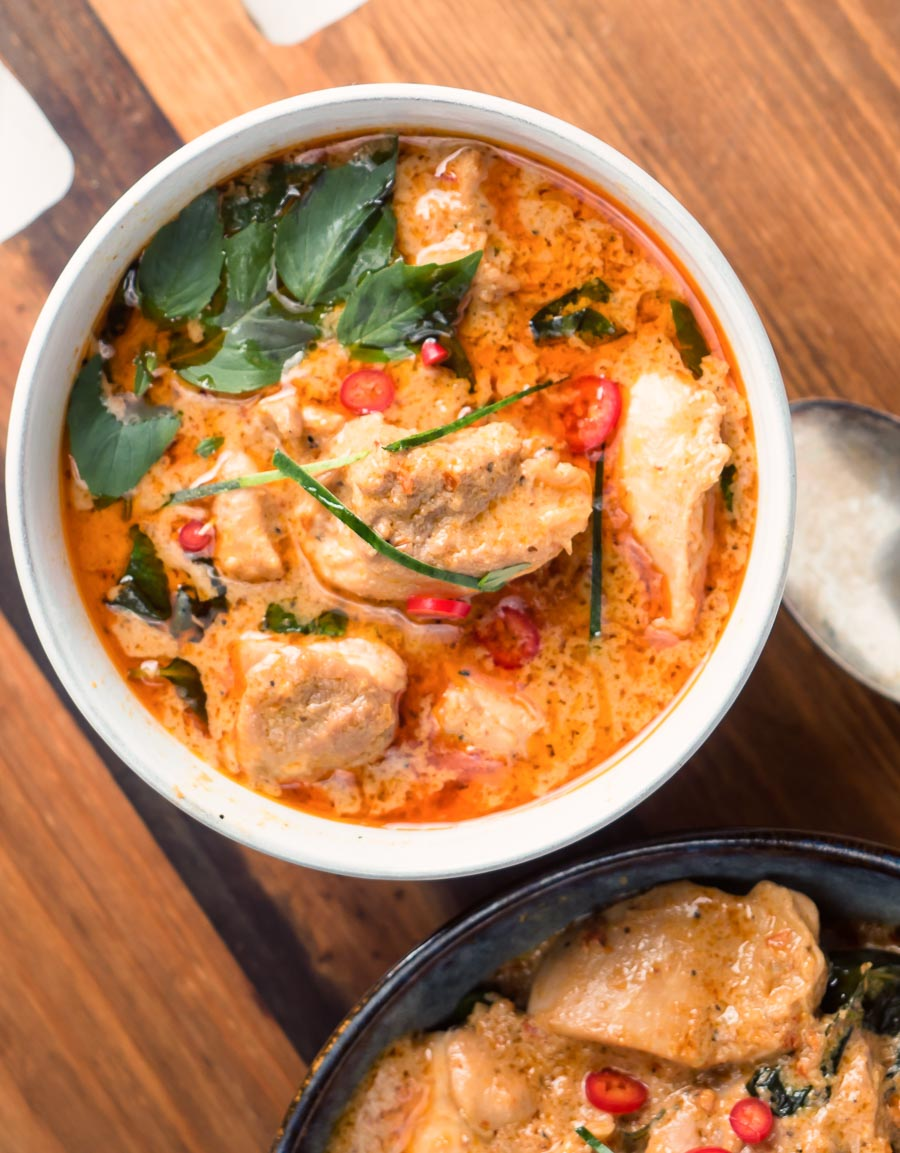 Panang curry garnished with basil and red chilies from above.