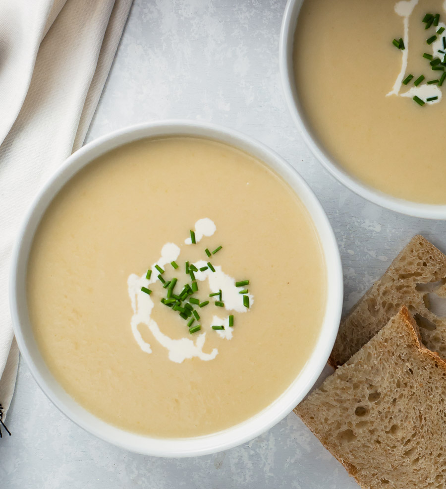 Potato leek soup garnished with cream drizzle and chives - from above.