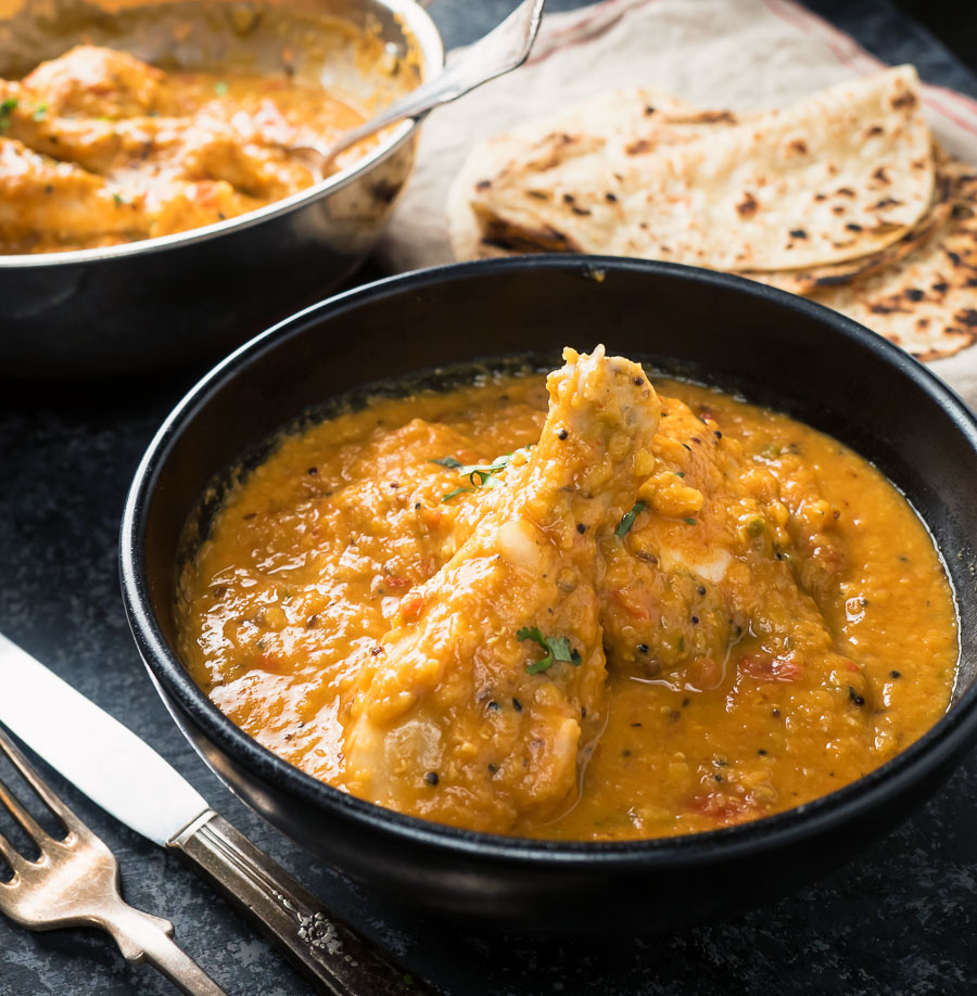 Chicken dhansak in a black bowl with paratha.
